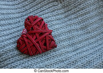 the red heart lies on the gray woolen fabric of the sweater