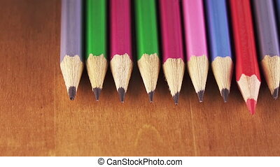 the red pencil lies among black lead pencils lie in a row