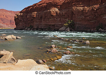 The stones in the shallows of the Colorado River in the red rocks of the desert