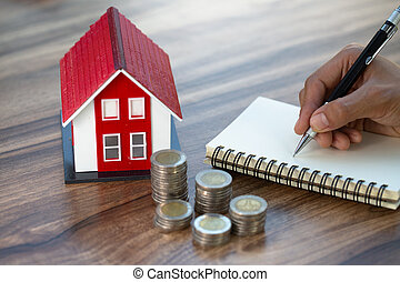 The red roof house and the pile of coins together with recording the income and expenses on the wooden table. Concept of saving money to buy a house for the future. Mortgage home and real estate.