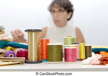 reels of colored threads, seamstress at the bottom
