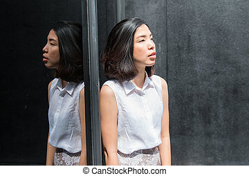 the reflection of asian young woman on the mirror