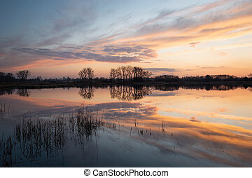 The reflection of colorful clouds and trees in a peaceful lake