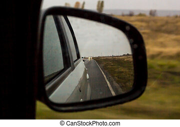 The reflection of road in the side view mirror with raindrops. Travel concept.