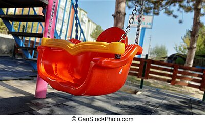 The reflection of the sun on the red swing in the park.