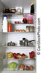 refrigerator - The refrigerator, filled with different food ...