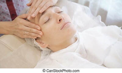 The rejuvenating massage for face in the beauty salon
