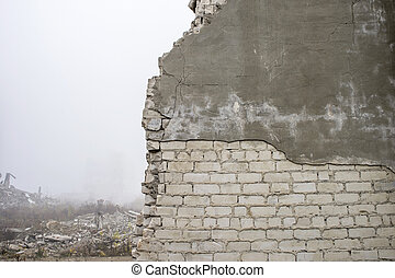 The remains of the destroyed wall of the building silicate white brick with partially peeling gray plaster solution.