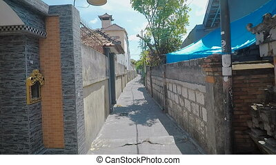 The review of the area to Bali. In the area of the house from a stone, green palm trees, iron gate, concrete walls and narrow expensive