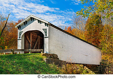 The Richland Creek Covered Bridge in rural Greene County Indiana is surrounded by colorful fall foliage on a sunny autumn day.