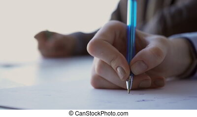 The right hand of the female student writes a final exam...