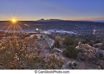 The rising sun, shining across an empty plain, lights an ancient Anasazi tower.
