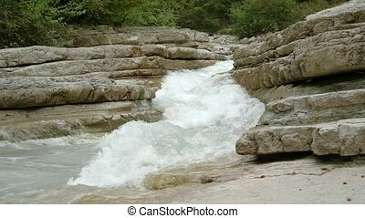 the river breaks through the rocks