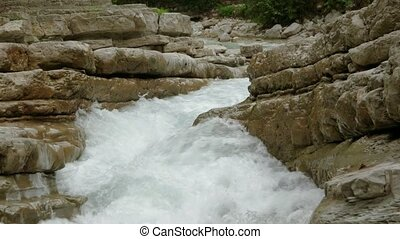 the river breaks through the stones