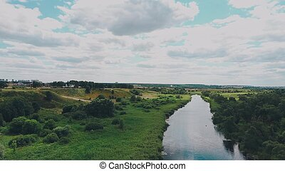 the river goes into the distance surrounded by green trees on a clear day