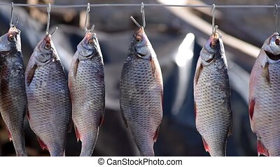 The river salted fish hangs on an iron jug and is dried