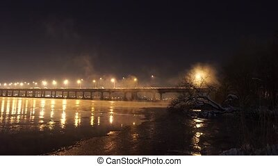 The river with illuminated half-bridge in winter night