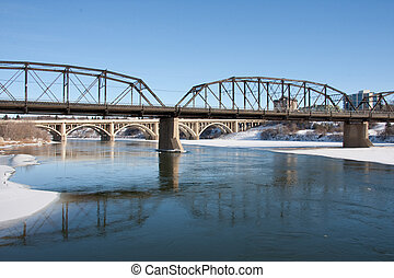 A view of the Victoria Bridge and Broadway Bridge in Saskatoon, Canada on a sunny day in winter.