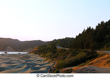 The road along the sandy beach of the Pacific Coast during sunset