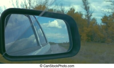 the road in the rearview mirror of the car slow motion video...