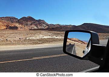 The road is reflected in the car mirror