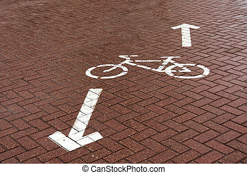 "The road sign ""Bike path"" is painted with white paint on the paving slab"