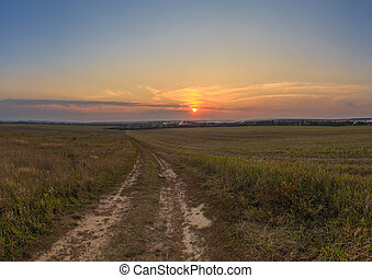 The road through the field with a hill at sunset