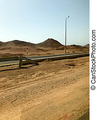 The roadside, highway with asphalt in the desert with sand, bumpers and lampposts, sand dunes, hills, mountains in a hot tropical country.