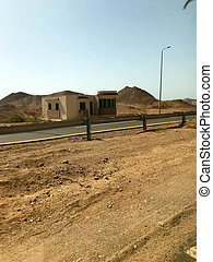 The roadside, road with asphalt in the desert with sand, bumpers and lampposts, sand dunes, hills, mountains and houses in a hot tropical country.