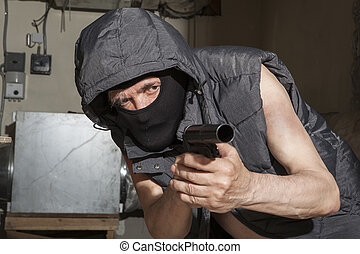 The robber armed with a gun in the