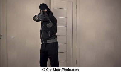 The robber climbed into the house. The masked bandit neatly went through the door to the room aiming a gun.