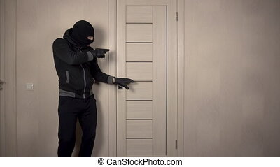 The robber climbed into the house. The masked thug carefully entered the door with a gun.