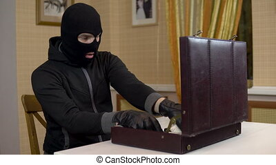 The robber opened the suitcase. A masked thug is sitting in ...