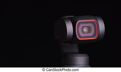 The robotic camera rotates in different directions. Security and object tracking. Macro. Mechanical gimbal camera lens rotates on black background, close-up. Portable camera with image stabilization.