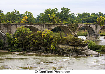 The Roche de Bout rock outcrop with the ruins of the Interurban bridge which crosses the Maumee river in Northwest Ohio.