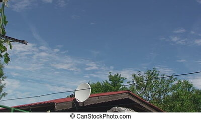 The roof of the house and across the sky fleeing clouds -...