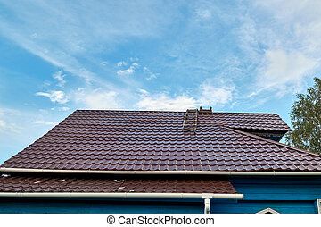 The roof of the village house is covered with new metal sheets. The sheets have a curved profile in the form of waves. Reliable and modern protection of the house from rain, snow and precipitation.