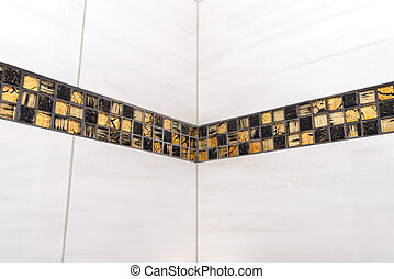 The room in the house is lined with classic ceramic tiles with a golden mosaic, tiles meet in the corner of the room.