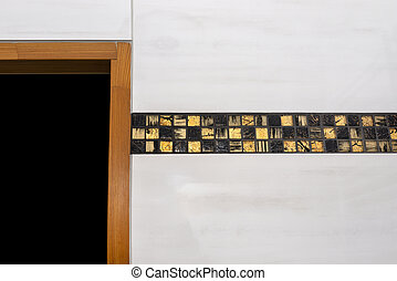 The room in the house is lined with classic ceramic tiles with a golden mosaic, visible wooden door frame.