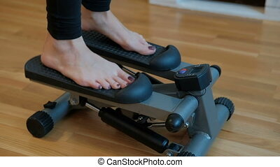 The room woman performs an exercise for the legs on the mini stepper.