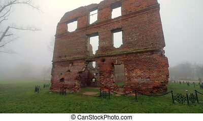 The ruins of an old red brick building. Everything is shrouded in thick fog.