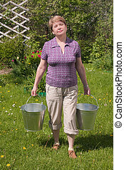 The rural woman with a bucket in hands
