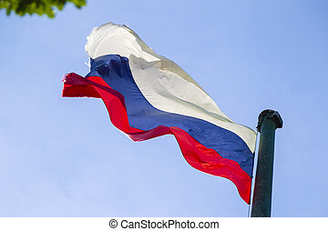 The Russian flag is developing on the flagpole