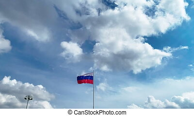 The Russian flag on lagpole is flying in wind