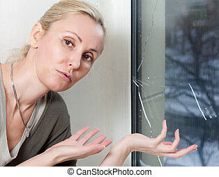 The sad young woman near a window with the burst, broken glass