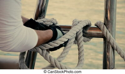 The sailor turns the rope on the yacht slow motion 50fps...