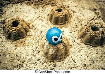 The Sandbox - A sandbox with sand cake and a rubber ball...