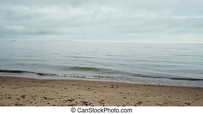 The sandy beach and the sea in cloudy day, Dolly shot