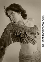 Young woman with wing across her breast. Sepia toned black and white photograph.