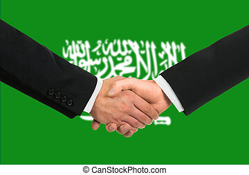 The Saudi Arabia flag and business handshake